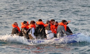 A small boat crammed with people wearing red life jackets