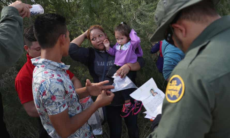 US border patrol agents prepare to take a group of Central American asylum seekers into custody on 12 June 2018 near McAllen, Texas.