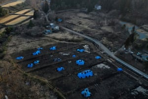 An aerial view of Kato's house standing close to a field that is being decontaminated in a restricted zone
