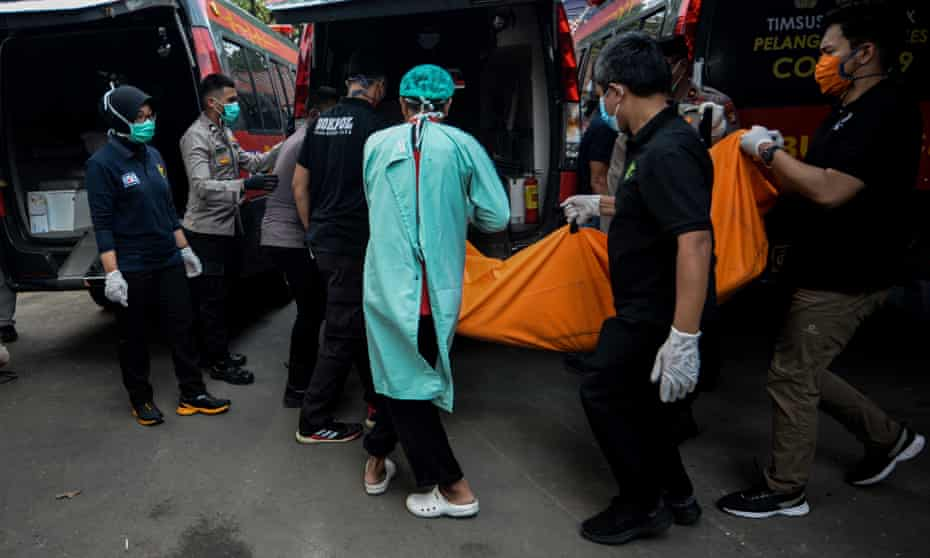 Police officers transfer a body bag of the victim of a prison fire in Tangerang, Indonesia.