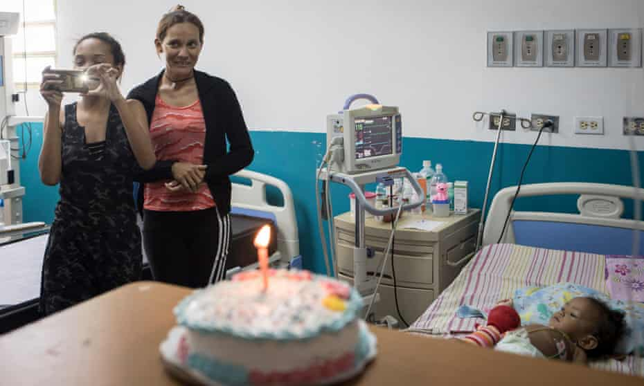 María and Alexandra smile as doctors sing happy birthday to Luciannys on her first birthday