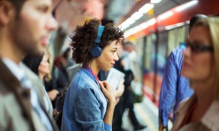 woman headphones london underground train