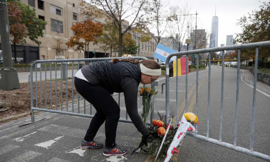 Natalie Kortman lays flowers for victims of Tuesday's attack outside a police barricade on the bike path next to West Street in New York City Wednesday.