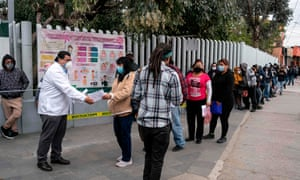 People who suspect they have Covid-19 line up for a second check at clinic in Tijuana, Mexico, on Monday.
