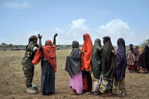 A female soldier of the African Union Mission in Somalia conducting a security check on a woman at a food distribution centre in Afgoye, Somalia.