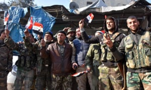 Pro-government forces hold Syrian flags in Aleppo's Bab al-Nairab neighbourhood on Saturday
