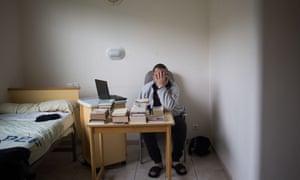 """A patient covers his face as he poses in his bedroom at the psychiatric hospital """"EPS de Ville Evrard, Centre psychiatrique du Bois de Bondy""""."""