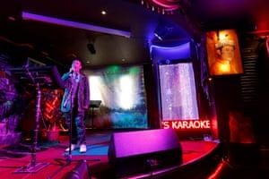 A man sings in a karaoke bar beside a portrait of King Jigme Khesar Namgyel Wangchuck.