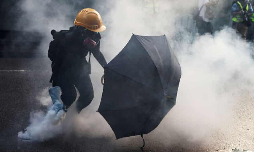 An anti-government protester picks up a tear gas canister during a demonstration in Hong Kong