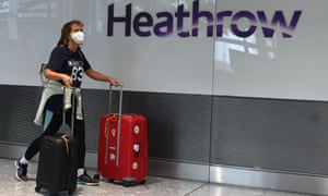 Passengers wearing a face mask or covering due to the Covid-19 pandemic, arrive at Heathrow airport