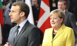Angela Merkel looks at France's President Emmanuel Macron as they arrive to attend the first day of the EU summit.