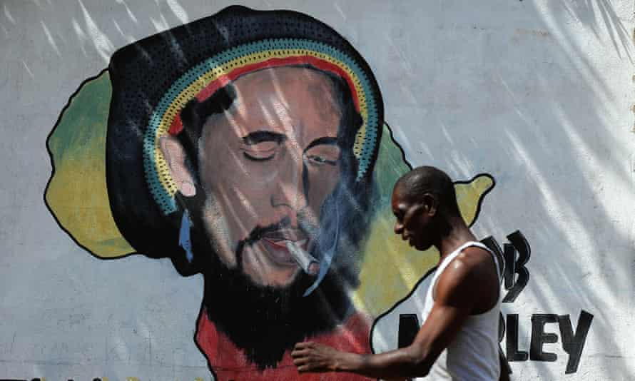A man walks past a mural of late reggae musician Bob Marley in Kingston.