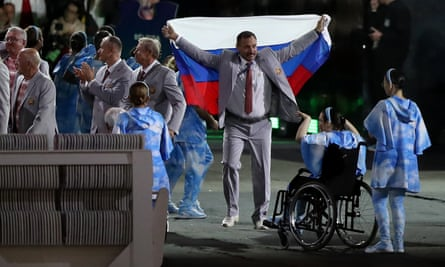 A member of the Belarus team carries a Russian flag.