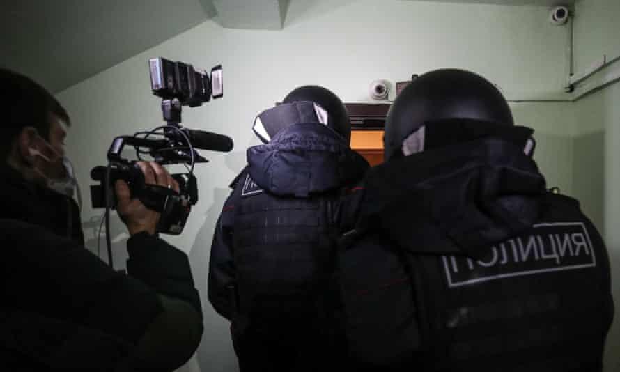 Police officers enter Alexei Navalny's apartment.