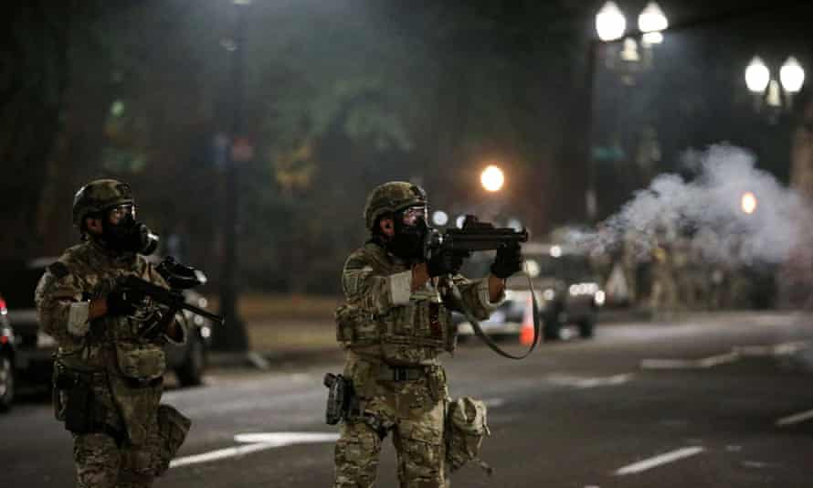A federal law enforcement official fires teargas at protesters in Portland, Oregon Sunday.