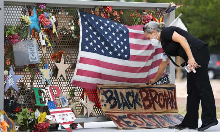A woman places a sign at a temporary memorial in Ponder Park honoring victims of the Walmart shooting which left 23 people dead in a racist attack targeting Latinos on 2 August 2020 in El Paso, Texas.
