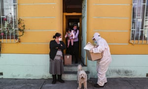A city worker, dressed in protective gear, delivers a box of food during a mandatory quarantine ordered by the government amid the new coronavirus pandemic in Santiago, Chile, 22 May 2020.
