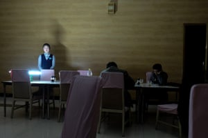 A waitress places a battery-powered light on the table during a night-time power outage in Chongjin. Blackouts are common and the customers barely notice as they continue to read and drinking fermented rice wine called makkoli