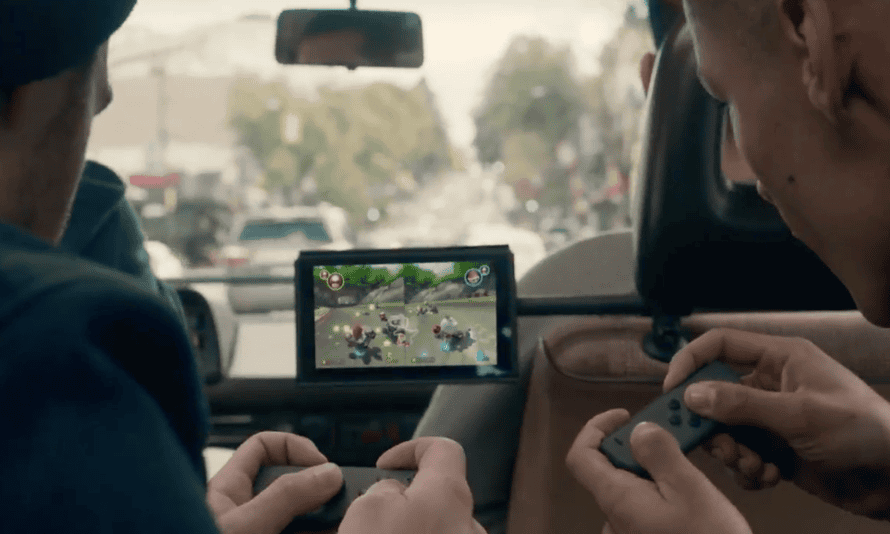 Two players play Mario Kart with the mini semi-controllers on the Nintendo Switch.