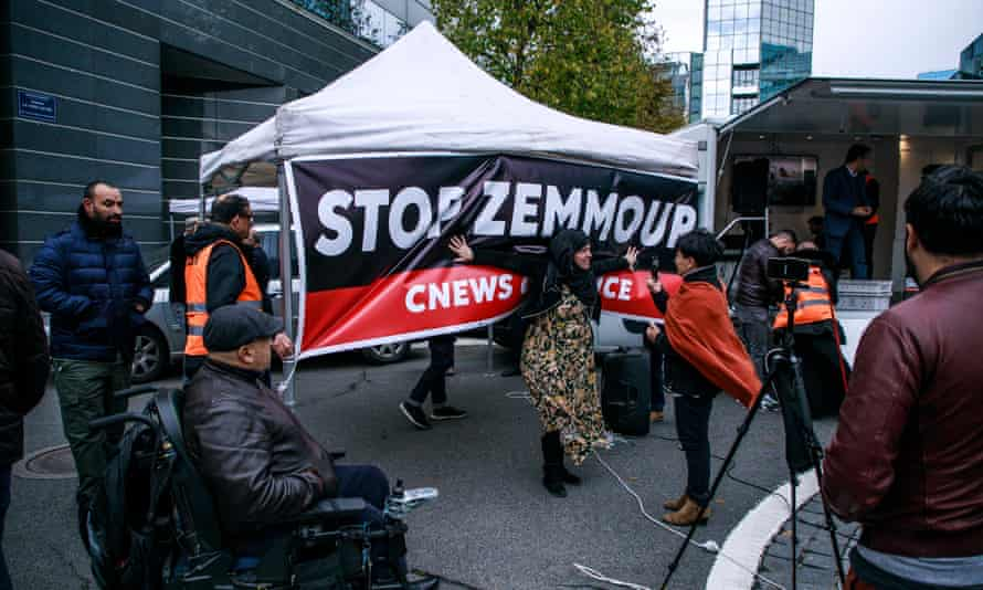 A woman poses in front of a banner reading 'Stop Zemmour'