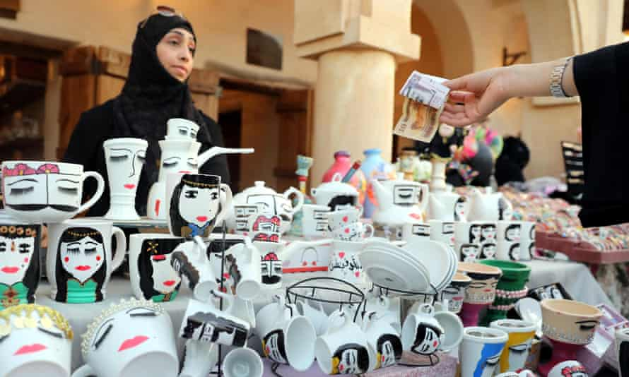 A woman sells painted coffee cups
