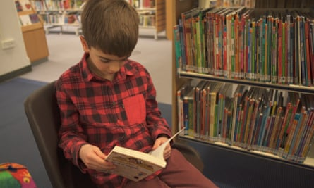 A boy reads a book at Chelmsford library in a promotional video for autism charity Dimensions.