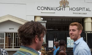 Dr Oliver Johnson, right, talks with a colleague outside the Connaught hospital in Freetown.