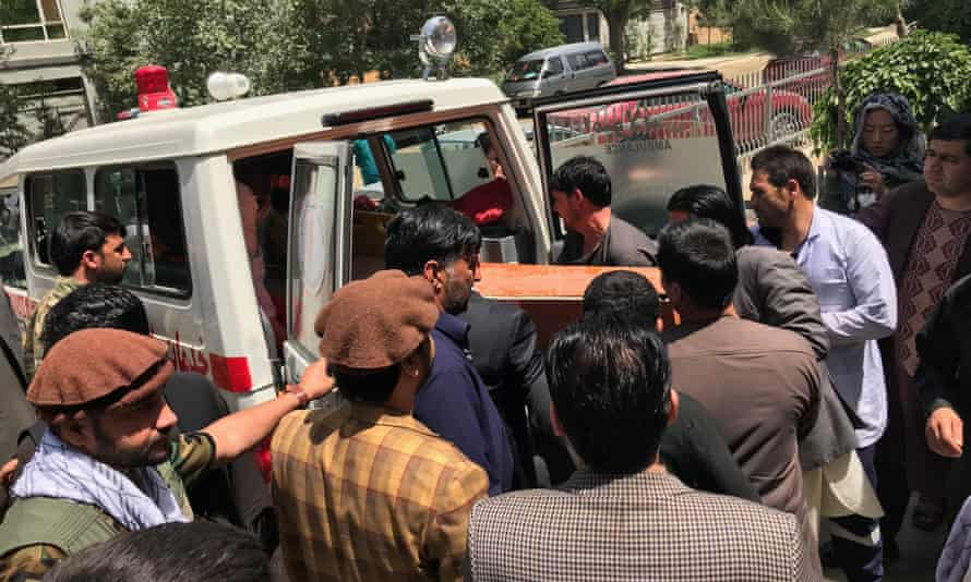 Relatives and friends lift a coffin containing the body of the Agence France-Presse photographer Shah Marai, who was killed in the twin bomb blasts in Kabul