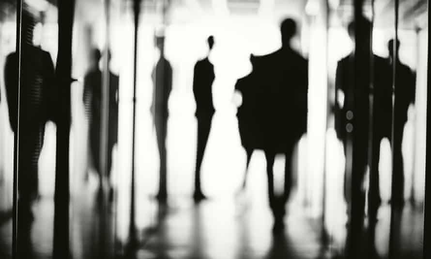 Office workers silhouetted in corridor.