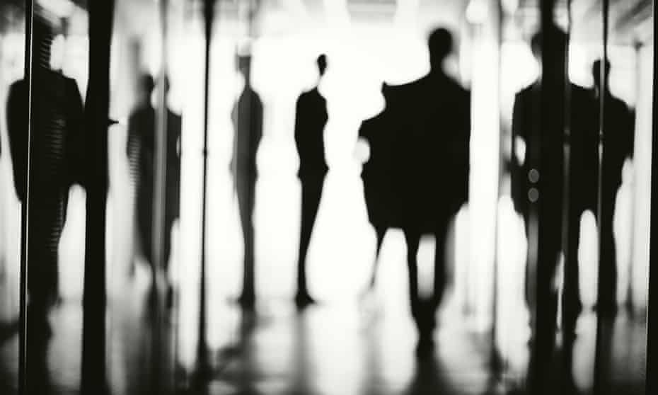 Silhouettes of workers in the corridor of an office