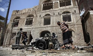 People stand amid the wreckage of a vehicle at the site of a car bomb attack near a military hospital in Sana'a, Yemen