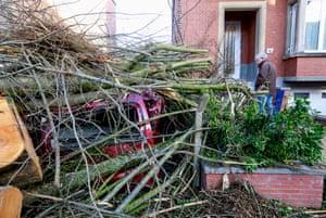 Un uomo guarda la sua macchina, che è stata schiacciata da un albero che cade a Bruxelles, in Belgio