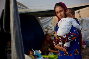 A young mother cradles her baby in front of a tent she is living in with two other families, at a camp for displaced people in northern Iraq