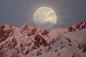 Full moon rises behind snow-covered mountains in Hakkari province of Turkey