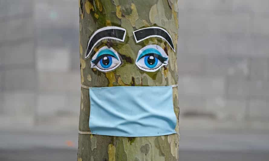 A tree decorated with a masked face in Melbourne, Australia.