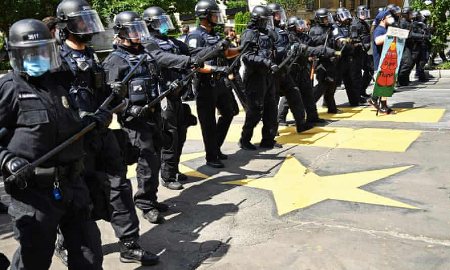 A line of police officers in riot gear move forward to form a security perimeter on 16th St NW near Black Lives Matter Plaza and Lafayette Square near the White House in Washington on 23 June.