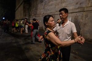 Couples dance next to the Yangtze river