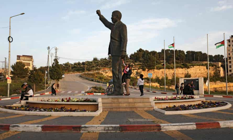 Palestinians walk next to a giant statue of Nelson Mandela in the West Bank city of Ramallah in March.