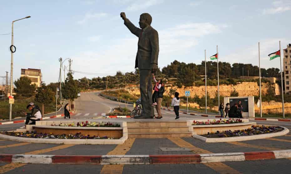 Los palestinos pasan junto a una estatua gigante de Nelson Mandela en la ciudad cisjordana de Ramallah en marzo.