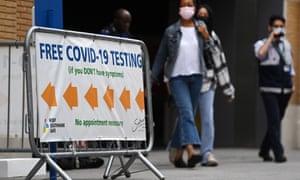 Pedestrians walk past a Covid-19 test centre in London.