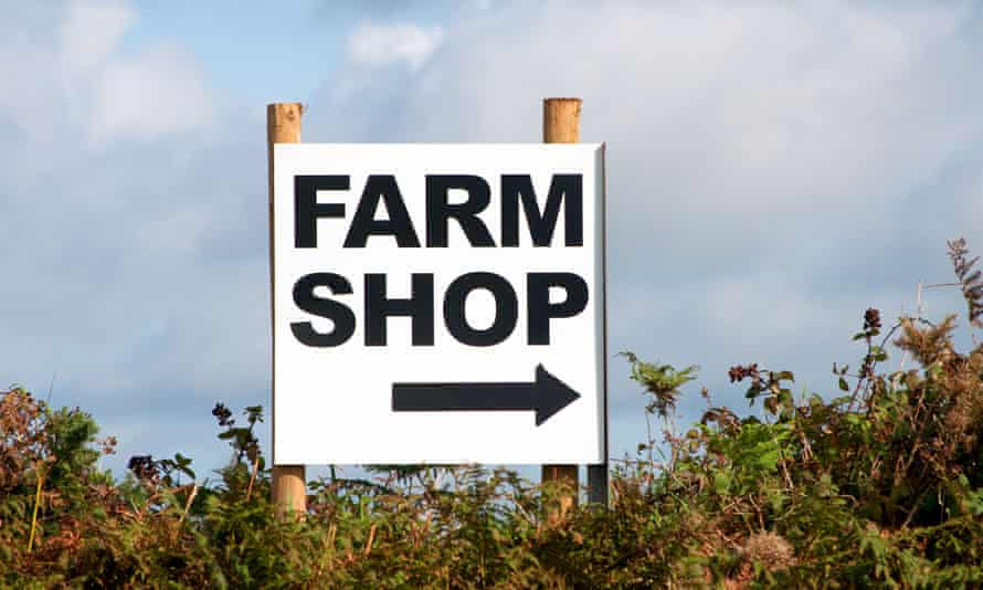 a farm shop sign in a hedge