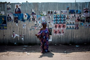 A woman signals for a taxi in front of a wall covered with campaign posters