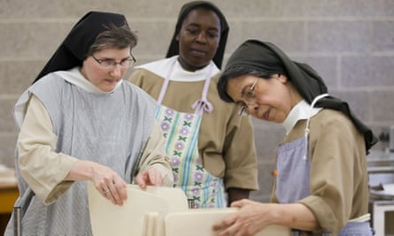 ister Anne Bartol, left, Sister Holy Spirit, and Sister Isabel, view uncut sheets of altar bread also known as communion wafers.