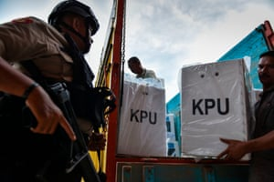 Indonesian police provide security as election workers transport ballot boxes to a polling station.