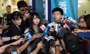 Demosisto leader Joshua Wong and member Agnes Chow speak to the press after they were released on bail in Wan Chai police headquarters in Hong Kong