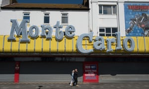 People walk past amusement arcades closed during the lockdown on a very quiet seafront in Southend on Sea.