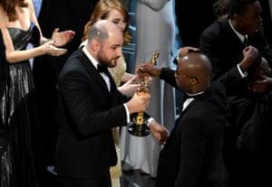 La La Land producer Jordan Horowitz hands over the Best Picture award to Moonlight writer/director Barry Jenkins following a presentation error onstage