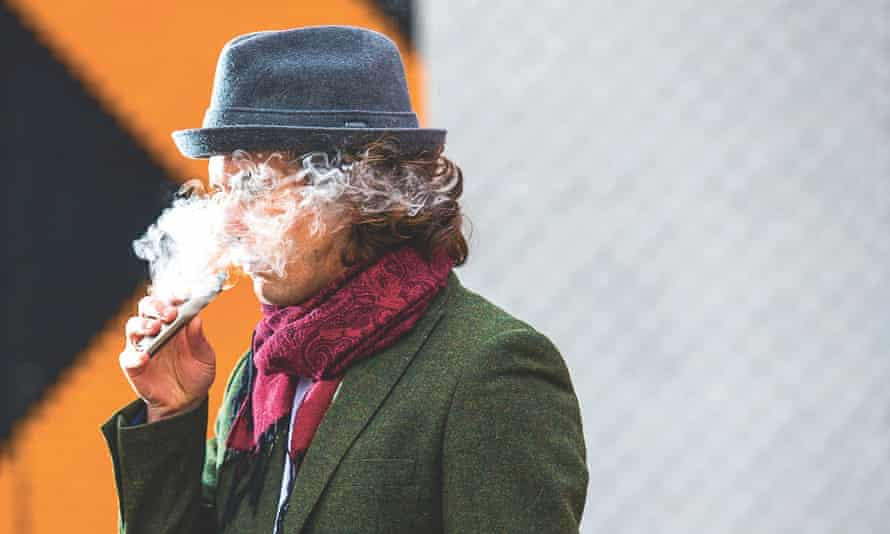Man wearing hat, face disguised by smoke