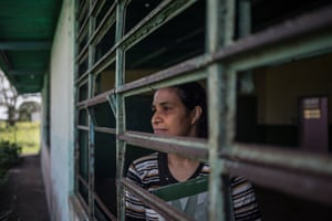 Parents' representative Silvia Márquez looks through one of the school's glassless windows. 'We're sick to the back teeth,' she said.