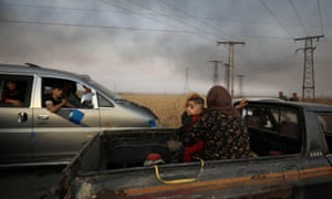 A woman with a baby flees Ras al Ain after Turkey launched its assault on Kurdish-controlled areas in northeastern Syria.